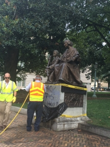 """Workers try to remove """"Black Lives Matter"""" graffiti on Confederate monument."""